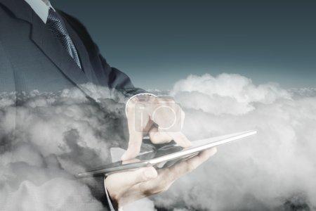 Photo pour Double exposition de la main de l'homme d'affaires en utilisant la tablette numérique avec le cloud comme concept - image libre de droit