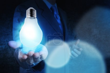 Light bulb in hand businessman on blue tone as concept