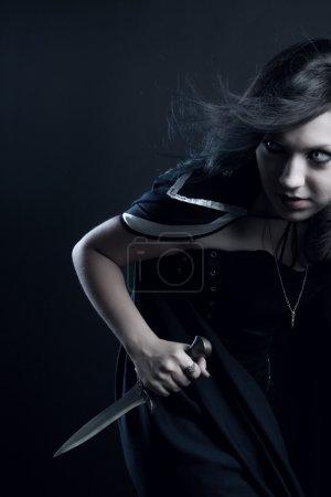 Girl with dagger posing over dark background...