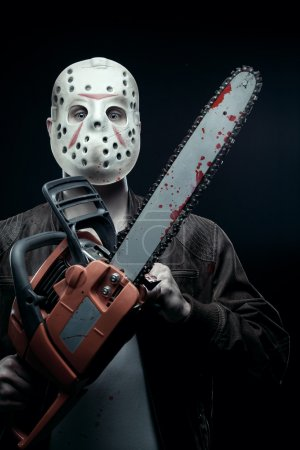 Photo for Maniac in mask holding bloody chainsaw - Royalty Free Image