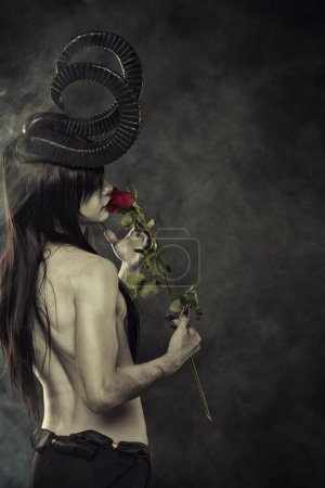 Photo for Horrible horned demon with red roses in smoke - Royalty Free Image