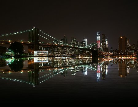 Brooklyn Bridge by night reflect in east river and new york skyline. freedom tower