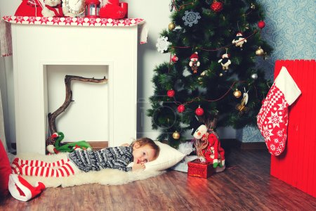 Girl laying under Christmas tree