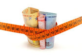 Concept od cuting cost with money and measuring tape