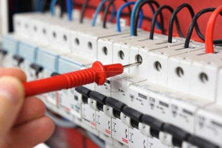 Photo pour Main d'un électricien avec multimètre sonde à une armoire de distribution électrique - image libre de droit