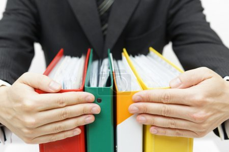 Photo for Businessman holding binders at office - Royalty Free Image