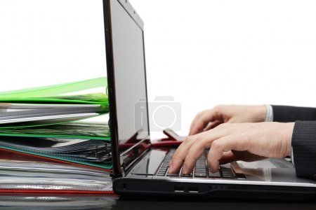 Accountant with full of documentation working on computer and us