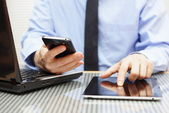 businessman is working on tablet and using smart phone in office