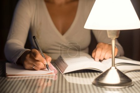 Photo pour Woman is studying and take notes late at night - image libre de droit