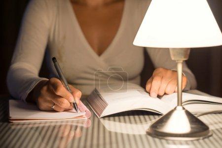 Photo pour Femme étudie et prend des notes tard dans la nuit - image libre de droit
