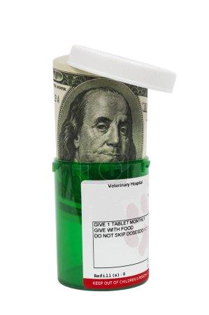 Photo pour Plan vertical d'une bouteille de médicament vert avec billet de cent dollars farci dedans montrant le concept de la façon dont les médicaments coûteux peuvent être même pour votre animal de compagnie. Isolé sur fond blanc . - image libre de droit