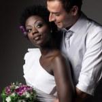 Multiracial wedding couple posing in a studio...