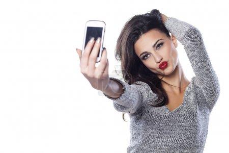 Photo pour Jolie fille faire un canard font face et prendre un autoportrait avec son téléphone intelligent - image libre de droit