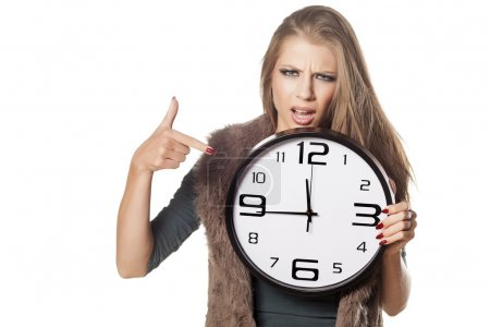 Photo for Angry young girl holding a big clock and pointing a finger at it - Royalty Free Image