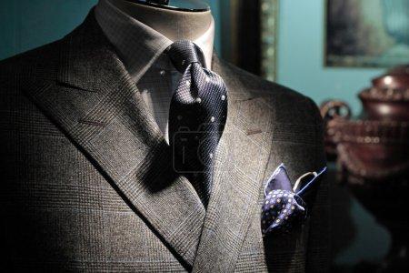 Grey checkered jacket, dark blue tie and handkerchiefGrey check