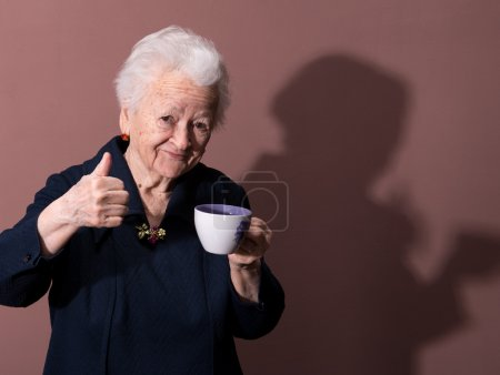 Photo for Old woman enjoying coffee or tea cup over brown background - Royalty Free Image