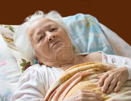 Old woman laying at bed