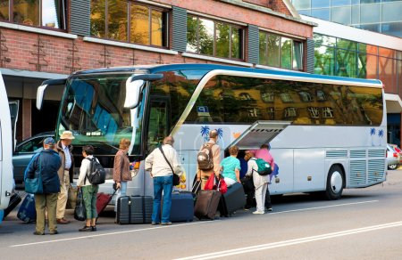 Photo for Bus for tourists transportation and group of tourists neat hotel - Royalty Free Image