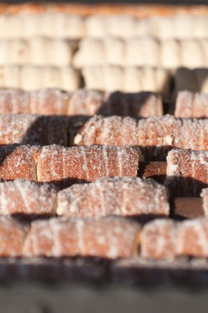 Sweet pastry Trdelnik during baking. Made from rol...