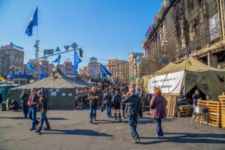 Photo pour Kiev, ukraine - 22 mars 2014 : les gens qui visitent la place maidan et des barricades sur la rue de khreshchatyk, sorcière dressent encore parce que les gens méfient de politiciens et attente pour les élections présidentielles. - image libre de droit