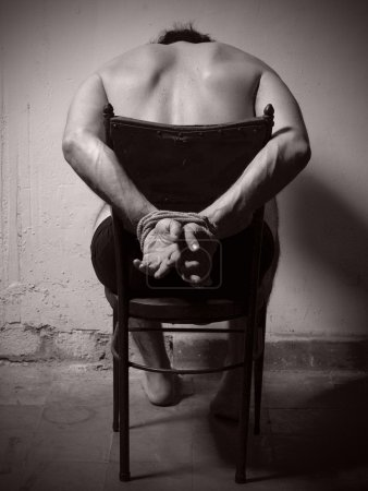 Photo for Torture man with tye hands and a chair. Vertical. - Royalty Free Image