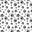 A random sized seamless pattern of dogs paws silho...