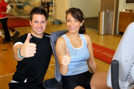 Trainer and woman on bike showing thumbs up