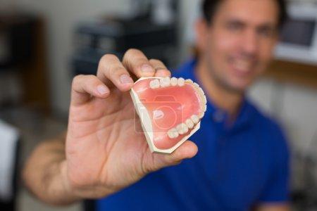 Dental technician presenting dental prosthesis