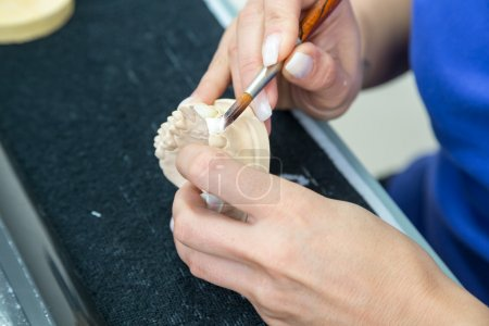 Technician in a dental laboratory applying ceramics to a prosthesis