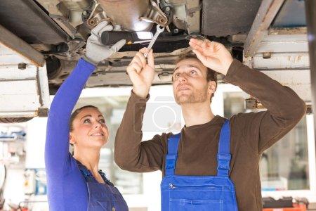 Two mechanics repairing a car in hydraulic lift