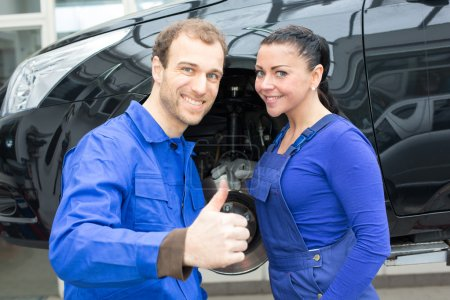 Two mechatronic technicians in garage with thumbs up