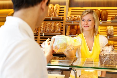 Photo for Bakery shopkeeper hands bag of bread over to customer - Royalty Free Image