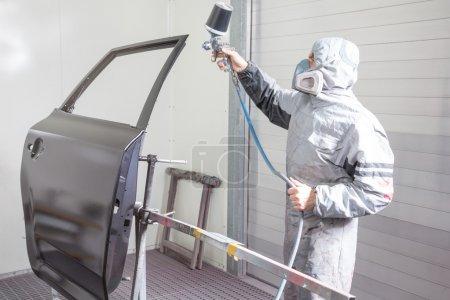Photo pour Peintre de carrosserie pulvérisation de peinture ou de couleur sur la carrosserie dans un garage ou un atelier avec un aérographe - image libre de droit