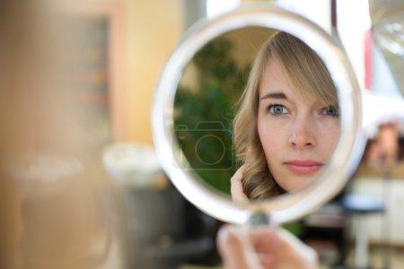 Client in hairdresser salon watches herself in mirror