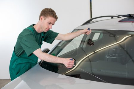 Photo for Glazier cutting adhesive of windscreen with a wire to replace windshield - Royalty Free Image