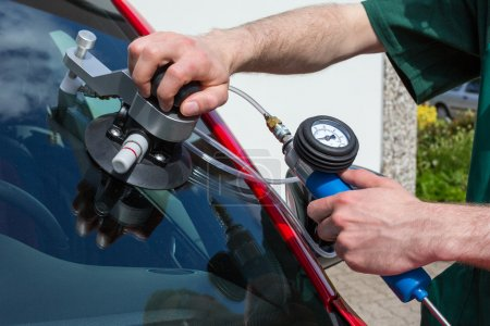 Photo for Glazier repairing windshield on a car after stone-chipping damage - Royalty Free Image