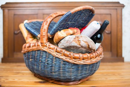 Picnic basket with croissants, bread, apples, salami and wine