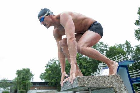 Swimmer standing on starting block at swimming pool