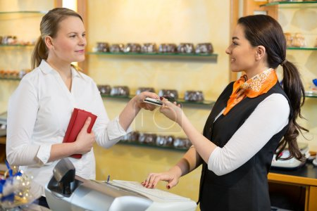 Photo for Client at shop paying at cash register with saleswoman - Royalty Free Image