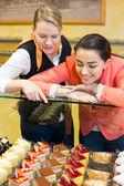 Zwei Frauen im Café Kuchen auswählen
