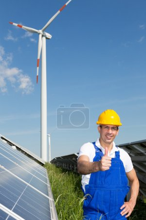 Foto de Ingeniero muestra pulgares hacia arriba en el parque de energía con paneles solares y turbina eólica - Imagen libre de derechos