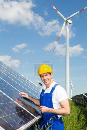 Foto de Ingeniero de inspección de paneles solares en el parque de energía frente a la turbina eólica - Imagen libre de derechos