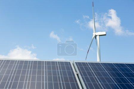 Foto de Una turbina eólica y paneles solares con cielo azul - Imagen libre de derechos
