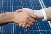 une poignée de main devant les panneaux d'énergie solaire