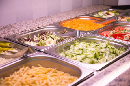 Salad, carrots and cucumbers on buffet at restaurant