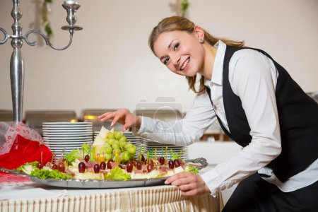 Catering service employee or waitress preparing a buffet