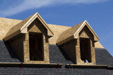 Photo pour Un gros plan tourné d'une maison de luxe en construction. montre un toit d'asphalte à moitié terminé avec deux fenêtres ouvertes. tourné avec un ciel bleu. - image libre de droit