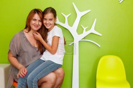 Photo pour Mère avec la fille, une fille de jung, sur ses genoux dans la salle d'attente médicale - image libre de droit