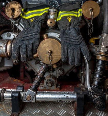 Photo pour Gants résistant au feu d'un pompier suspendus sur la greffe de tuyaux d'incendie d'un camion de pompier ancien. - image libre de droit