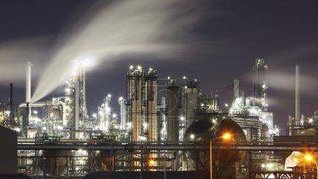 Foto de Refinería de petróleo y gas al atardecer con reflexión - fábrica - planta petroquímica - Imagen libre de derechos